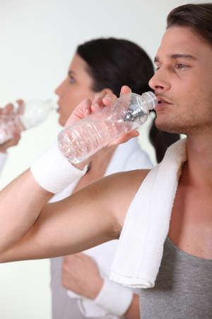 Couple drinking water after a hard gym workout photo