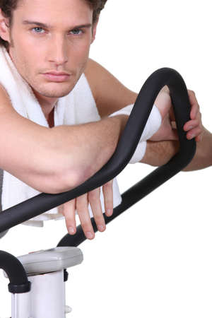 manly man: Man posing with an exercise machine