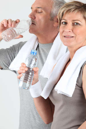 get a workout: senior couple drinking water after training Stock Photo