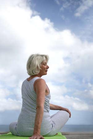 протяжение: Старший женщина делает йоги на открытом воздухе