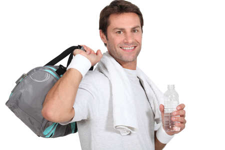 A sportsman smiling at us and holding a bag and a bottle of water. photo