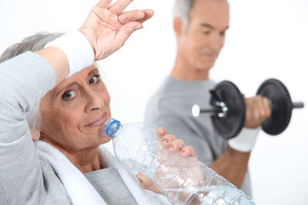 elderly exercise: Elderly woman drinking water after gym session