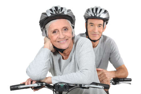 An elderly couple riding their bikes together photo