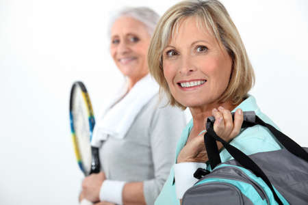 age forty: Two mature women playing tennis. Stock Photo