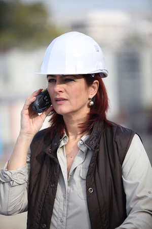 beautiful middle aged woman: middleaged female architect making a call in construction site