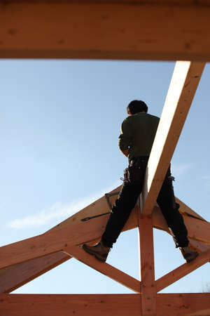 roof beam: Builder sitting on a beam Stock Photo
