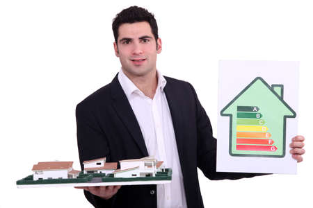 norm: Architect holding model housing and energy rating panel