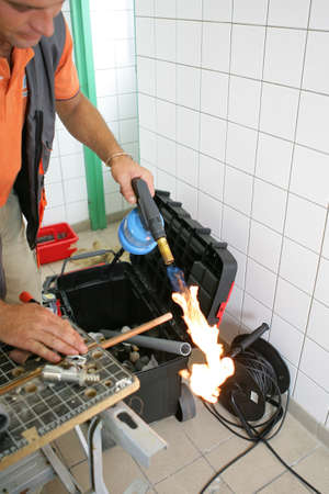 Plumber heating up copper pipe photo