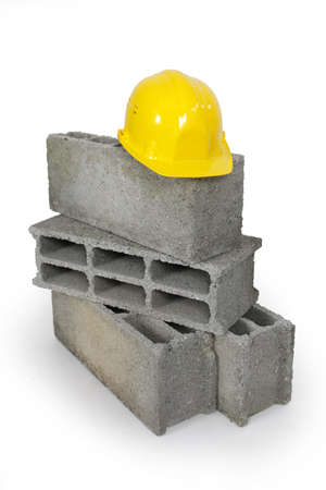 skilled labour: Yellow hard hat resting on pile of breeze blocks