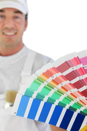 refurbishing: Male decorator holding paint swatch