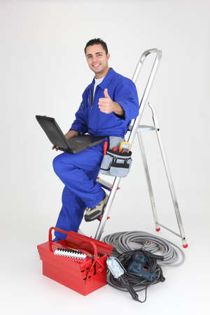 journeyman technician: Male electrician with laptop and equipment Stock Photo