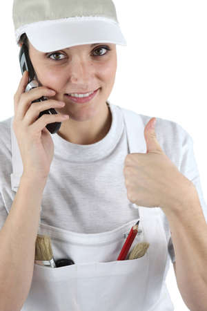 concurrence: Tradeswoman talking on her mobile phone and giving the thumbs up Stock Photo