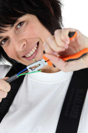 disconnecting: Woman pulling wires using a pair of pliers Stock Photo