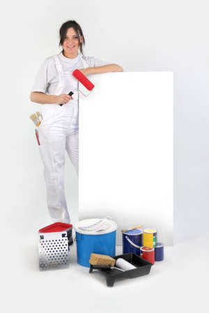 housepainter: Decorator stood by blank advertisement board holding roller