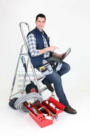 step ladder: Electrician perched on step ladder Stock Photo