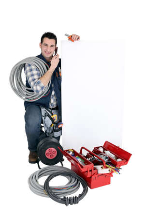 Tradesman posing with a blank sign and his tools photo