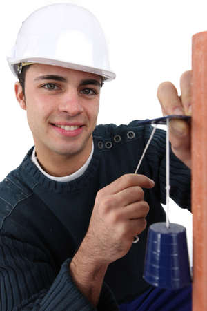 portrait of young bricklayer installing bell photo