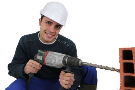 Man drilling through brick photo