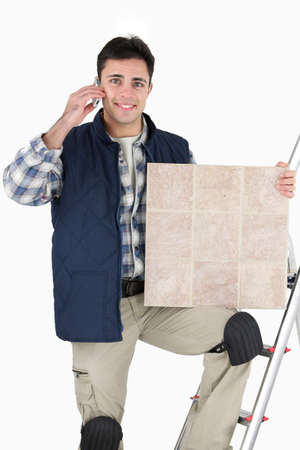 answering phone: Tiler respondiendo a la llamada de tel�fono de los clientes Foto de archivo
