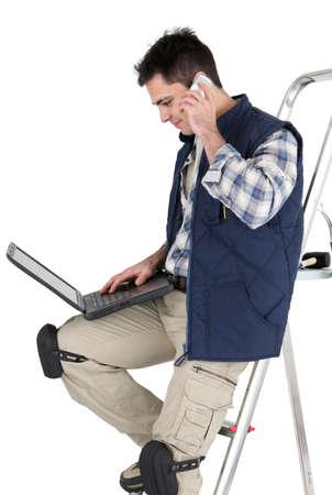 journeyman technician: Tiler with a laptop Stock Photo