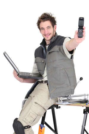 Tradesman holding a mobile phone and a laptop Stock Photo - 16950156