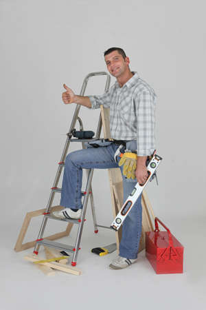 Carpenter stood by ladder giving the thumbs-up photo