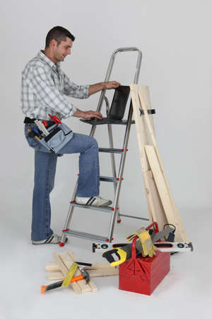 Carpenter using a laptop whilst stood by ladder Stock Photo - 16950778