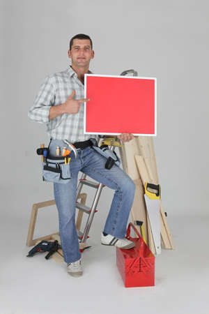 Carpenter holding a blank red sign photo