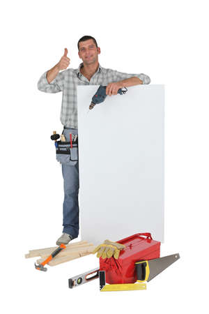 Approving tradesman posing with a blank sign and his tools photo