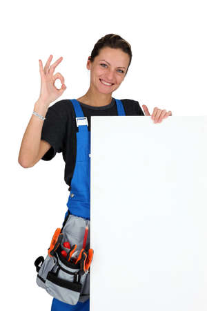 Female  construction worker with tool belt and a board left blank for your message Stock Photo