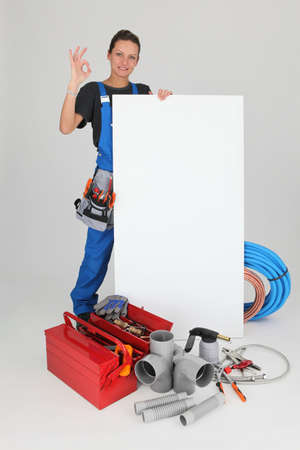 Female plumber with tools of the trade and a board left blank for your message photo