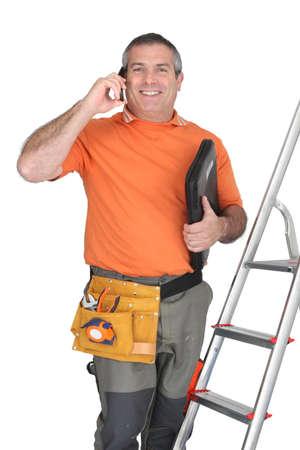 outils plomberie: L'homme au t�l�phone cellulaire avec des outils d'�chelle et de la plomberie