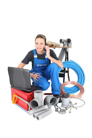 workwoman: Tradeswoman surrounded by building materials and technology Stock Photo