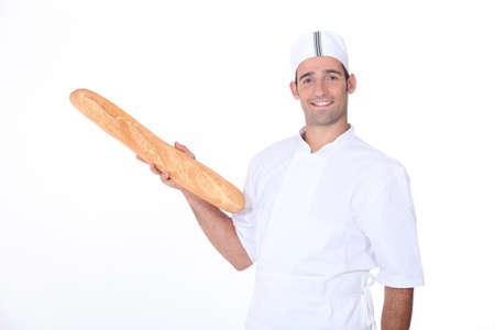 early 30s: Baker holding fresh baguette Stock Photo