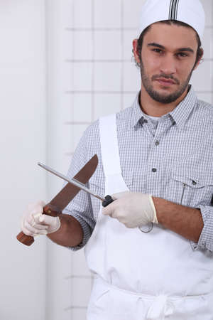 honing: Young cook sharpening knives
