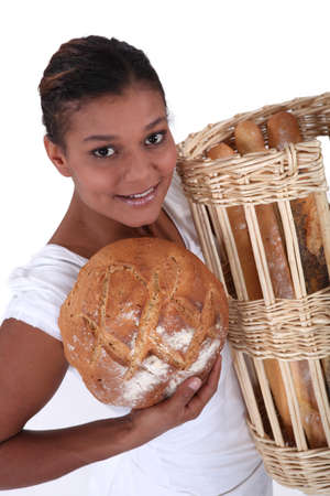 Female baker holding bread, studio shot photo