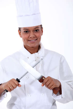 Chef sharpening a kitchen knife with a steel photo