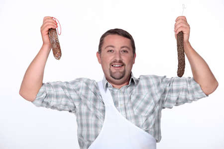 butcher holding fresh sausages photo