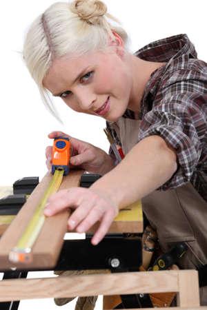 servicewoman: A female carpenter measuring.