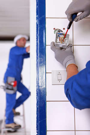 improvement: An electrician fixing an outlet  Stock Photo