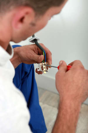 Electrician installing electrical outlet photo