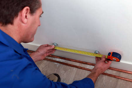 Plumber measuring length of copper pipe photo