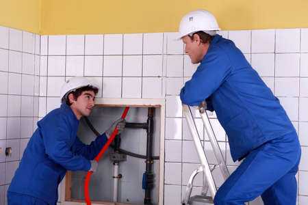 flexi: Apprentice passing red cable up behind a tiled wall Stock Photo