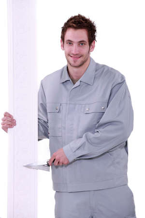 capping: Man holding a trowel and decorative crown moulding Stock Photo