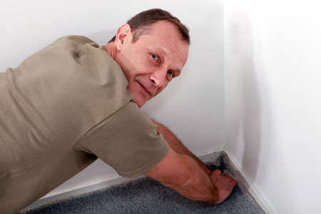 45 49 years: Man fitting carpet into a corner Stock Photo