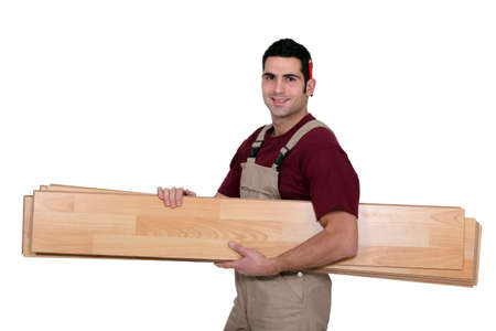 Worker carrying wooden planks photo