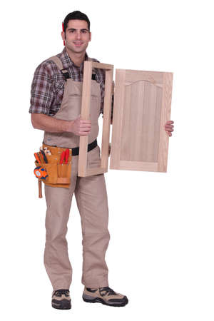 joiner: carpenter holding a wooden window frame Stock Photo