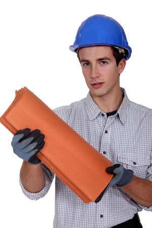 Construction worker holding roof shingles photo