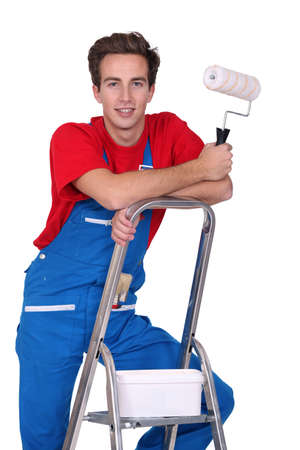 3 persons only: Decorator standing on a ladder Stock Photo