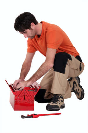 Man searching for a tool in his toolbox photo